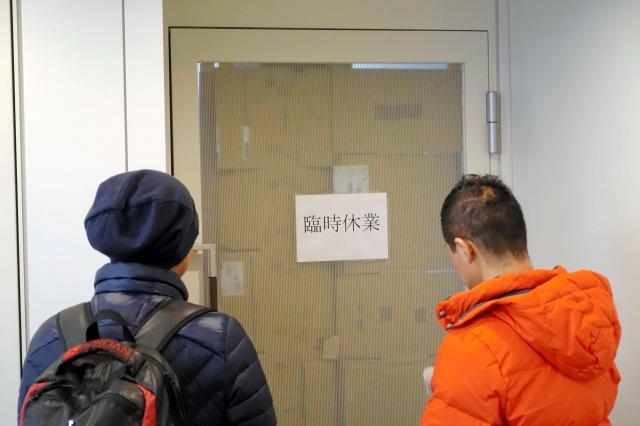 発券を巡るトラブルを起こした旅行会社「てるみくらぶ」の本社があるビルには利用者が集まった。会社の扉には「臨時休業」と書かれた紙が張られていた=2017年3月25日、東京都渋谷区