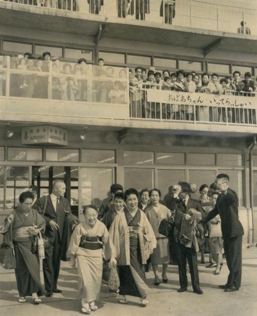 飛行機に向かう一般海外旅行第一陣。空港2階には「おばあちゃんいってらっしゃい」の横断幕が=羽田空港
