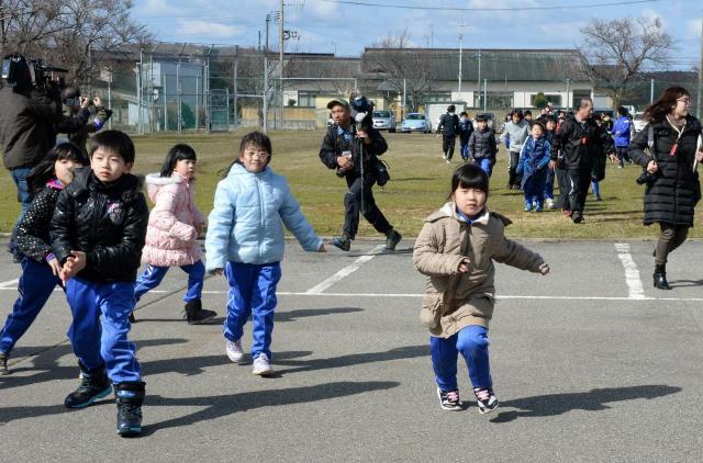 秋田県男鹿市の北陽小学校であった、ミサイル落下を想定した訓練。子どもたちは校庭から屋内に避難=2017年3月17日