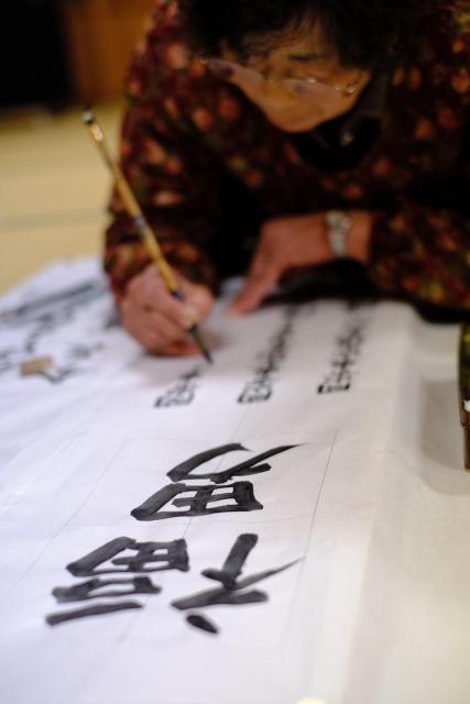 寺の鐘桜門に飾る行灯用に福男の名前を書く女性。深夜まで作業は続いた