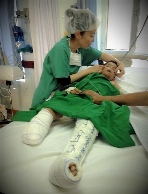 空爆で足の切断という重傷を負った男の子を治療する白川さん(左)