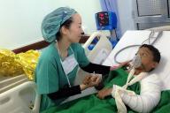 空爆でケガを負った子どもを診察する白川優子さん(左)=イエメン