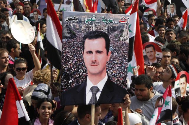 シリアの首都ダマスカスで、バッシャール・アサド大統領のポスターを掲げるアサド政権支持者=2011年10月26日