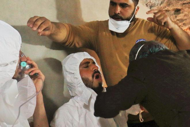 シリア北西部イドリブ県で、毒ガスとみられる攻撃を受け、救助隊の処置を受ける男性(中央)。左の男性は酸素マスクを着けている=2017年4月4日、ロイター