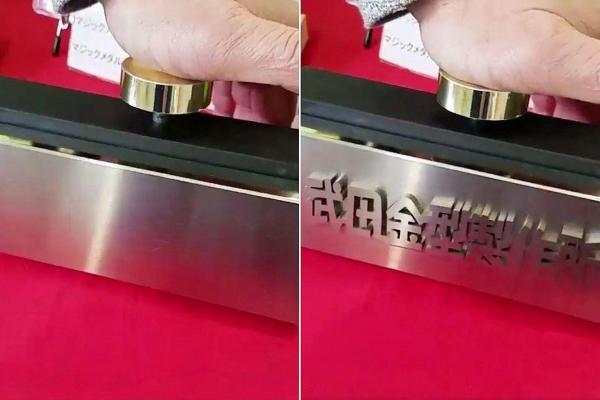 ネットで話題になっている金属板の動画。ボタンを押すと「武田金型製作所」が浮かび、離すと消える