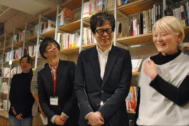 当事者のインタビューをまとめた『顔ニモマケズ』(文響社)の出版記念イベントで当事者の人々と記念撮影に応じる著者の水野さん(後列右)