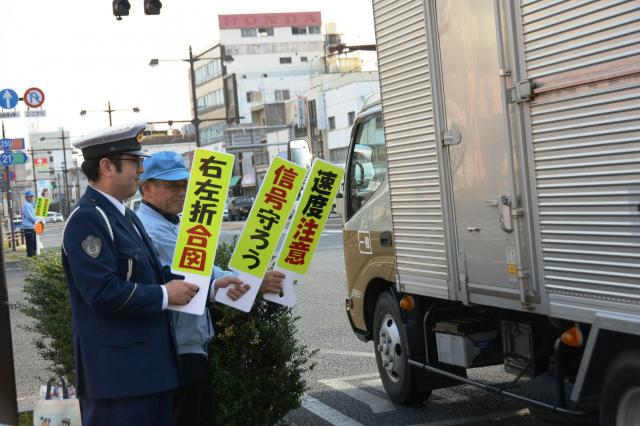 岡山市内の路上に立ってプラカードでウィンカーを出すよう呼びかけ