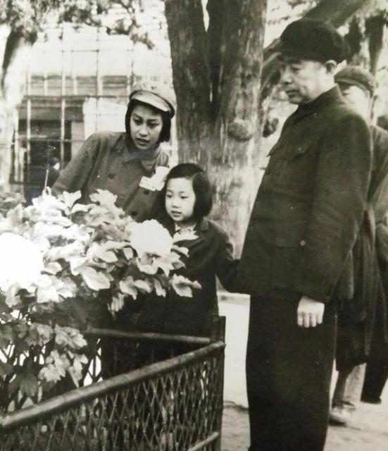 周恩来(右)と一緒に芍薬の花見をする幼少時代の周秉宜さん(中央)