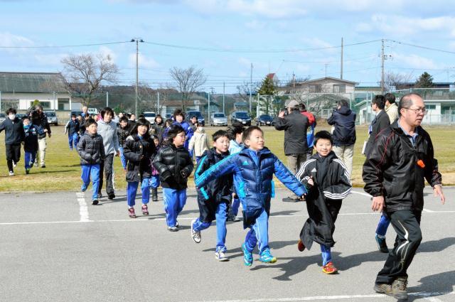弾道ミサイル落下を想定した訓練で、校庭から屋内へ避難する児童たち=3月17日、秋田県男鹿市の北陽小学校、迫和義撮影