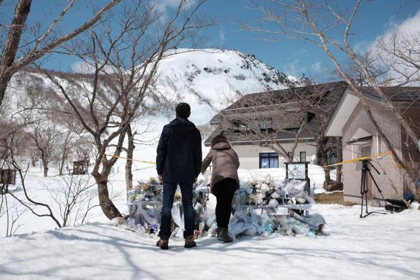 雪崩の犠牲者を悼む献花台の先に事故現場となった雪山がそびえる=4月3日、栃木県那須町
