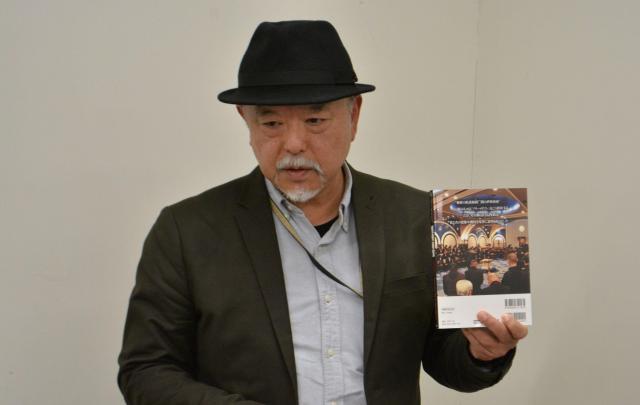 日本のグランドロッジの写真が掲載された本「怪奇秘宝戦慄編 」(洋泉社MOOK)を手に、フリーメイソンについて語る皆神さん
