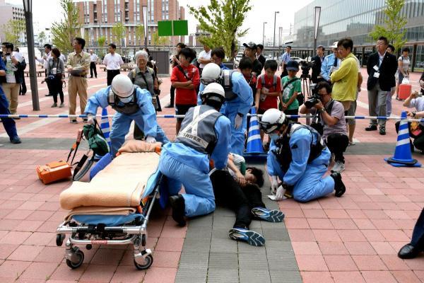 けが人を救助する訓練をする救急隊員=2016年7月、JR旭川駅北広場