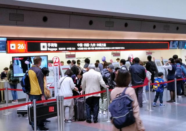 空港でカウンターに並ぶ人々