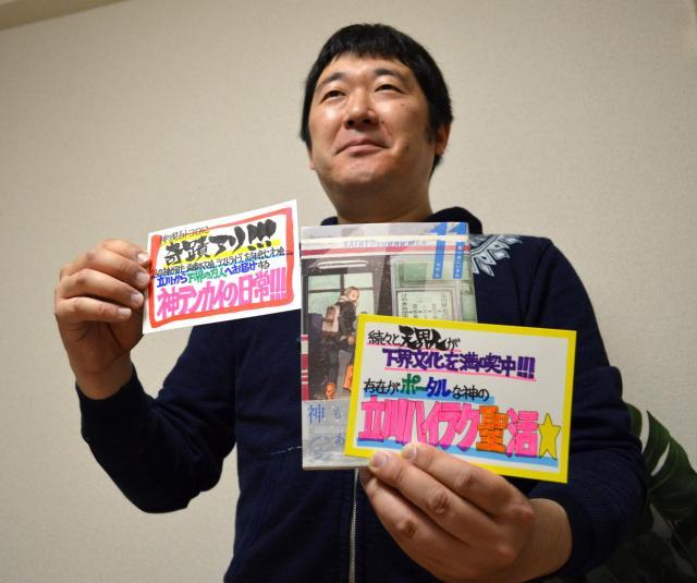 イエスとブッダが現代の東京で休暇過ごす『聖☆おにいさん』11巻と13巻のPOPを手にするはりまさん。右手に持つPOP(13巻)は、記念すべき1万枚目だそうです