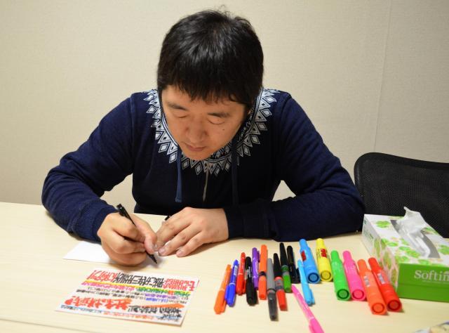 「書き直しますか?」と自ら提案し、改めて稀勢の里のPOPを書くはりまさん。筆ペンや油性・水性ペンを使います