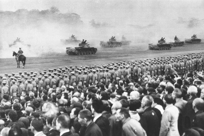 天長節(昭和天皇の誕生日)の観兵式に招かれ、戦車部隊の行進を見る戦没者の遺族たち。行進するのは97式中戦車(チハ車)=1941年4月29日