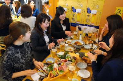 仕事を早めに切り上げてビールなど食事を楽しむ人たち=2月24日午後4時21分、大阪市北区