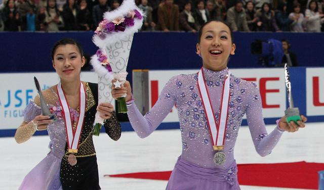 2010年全日本選手権で表彰式後にリンクを回り、スタンドの声援に応える浅田真央(右)と村上佳菜子=2010年12月26日、上田潤撮影
