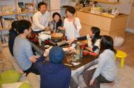 シェアハウスの住人や友人らと鍋を囲む(奥左から)栗山和基さん、妻の奈央美さん、阿部珠恵さん=東京都新宿区