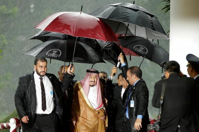サウジアラビアのサルマン国王(中央)が雨に濡れないよう、傘を差すおつきの人たち=2017年3月1日