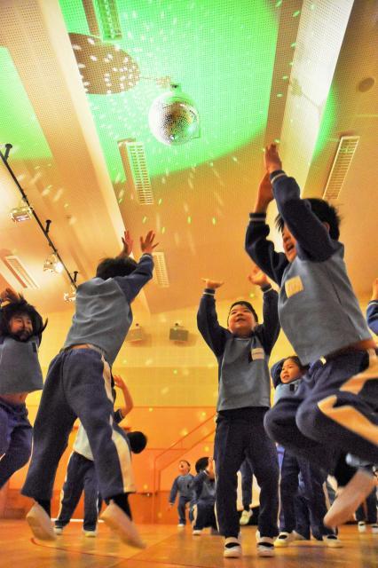 ミラーボールの光で遊ぶ千里丘学園幼稚園の園児たち=大阪府吹田市