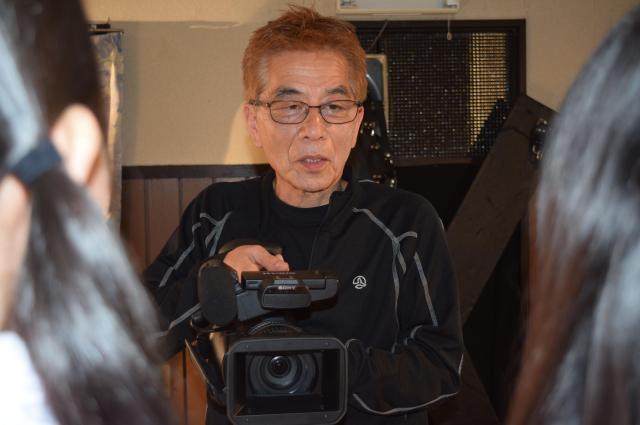 カメラを手に持ちながら、2人のAV女優に向き合う安達監督