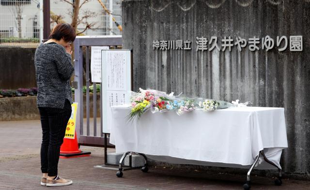 津久井やまゆり園の献花台を訪れ、祈りを捧げる人=2016年12月26日、相模原市緑区、葛谷晋吾撮影