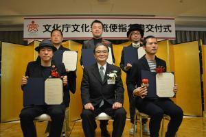 増田セバスチャンさん(右奥)ら2017年度の文化交流使5人と、宮田亮平・文化庁長官(中央手前)=17日、東京・霞が関