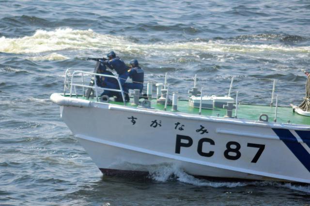 テロリスト役の銃撃に海上保安官らが「正当防衛射撃」で応じる訓練=5月20日、東京湾