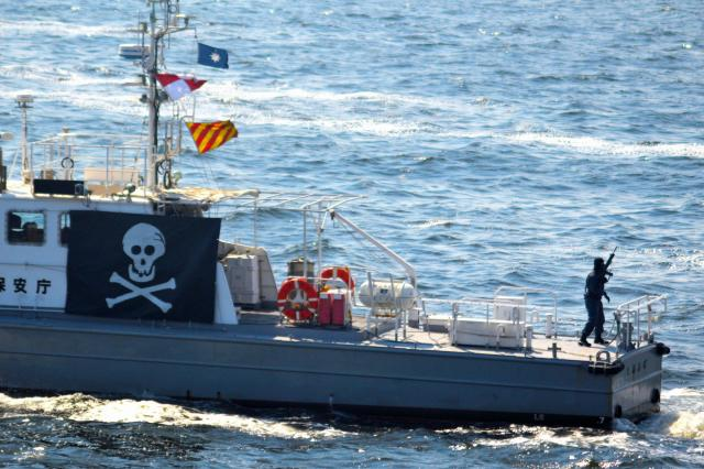 「容疑船」の甲板にテロリスト役が現れ、海上保安庁の巡視艇に向けてライフル銃を撃つという想定の訓練=5月20日、東京湾