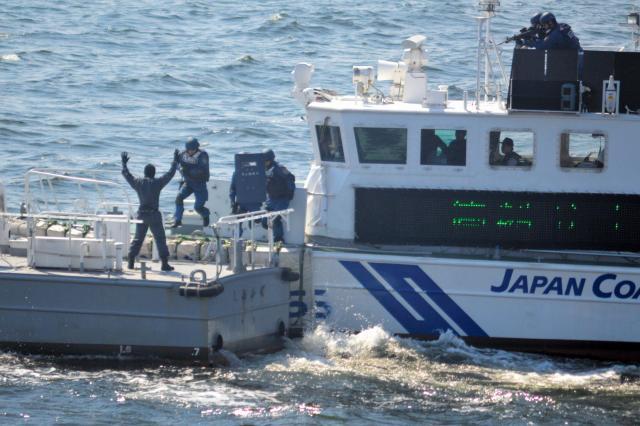 テロリスト役が手を挙げて降参。逮捕のため海上保安庁の巡視艇「いそぎく」から海上保安官が「容疑船」に飛び乗る。巡視艇からは別の海上保安官(右上)がテロリスト役を銃で狙う=5月20日、東京湾