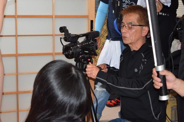 照明スタッフやADに囲まれ、カメラのモニターをチェックする安達かおる監督