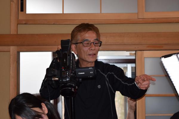 撮影現場でカメラを片手に、スタッフに指示を出す安達監督