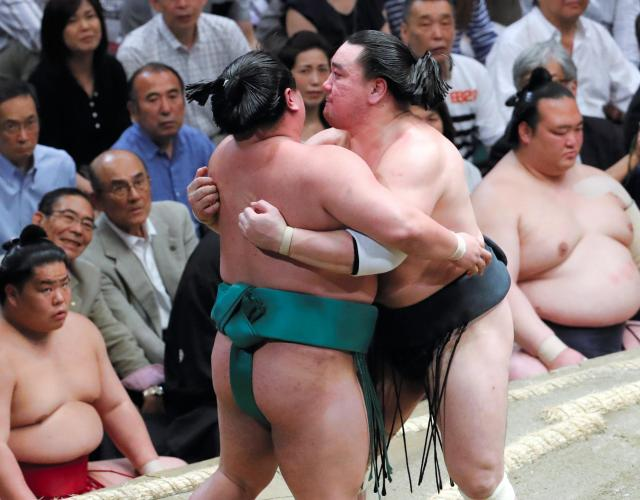 日馬富士(右)は嘉風を押し出した後、土俵下に落ちないよう抱き留める=越田省吾撮影