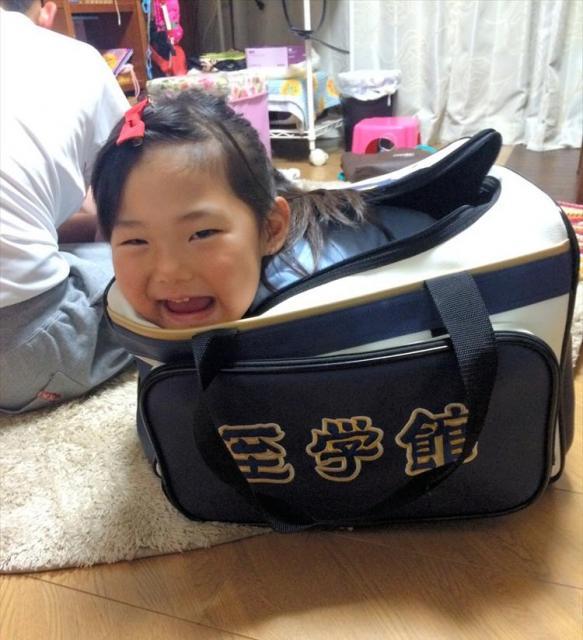 兄・和輝くんの至学館の新しいかばんに入って遊ぶ4歳の那奈夏さん=林由里子さん提供