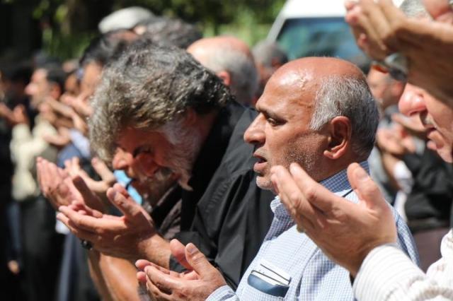 イランの首都テヘランのモスクの外で、神に祈りを捧げる男性たち=2016年9月9日