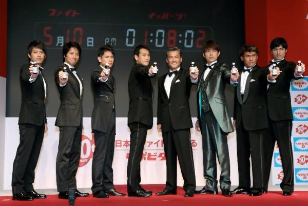 「リポビタンD」の発売50周年を記念して、「5月10日午後1時8分2秒(ファイト イッパーツ!)」に商品を掲げる歴代のCM出演者たち=2012年5月