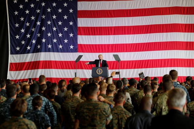 シチリア島のシゴネラ空軍基地で、巨大な星条旗を背に演説するトランプ米大統領=2017年5月27日