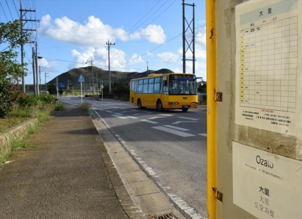 1日5本前後のバスが止まる「大里」バス停。時刻表の下に外国語表記が並ぶ。反対車線側の表記は消えていた=2014年11月、沖縄県石垣市桃里 、赤井陽介撮影