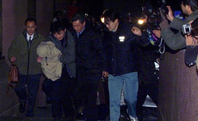 フードをかぶり、弘前署に連行される「武富士事件」の容疑者(2002年)