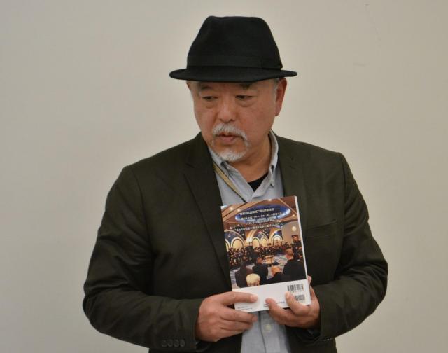 皆神龍太郎さん。手にしているのは日本のフリーメイソン内部の写真が載った本