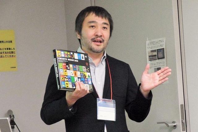 「50億個」といわれる収集品を残した柳本さん。手にしているのは、自身が出版したブックデザイナー時代のディック・ブルーナさんの作品集=2014年11月