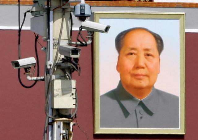 天安門広場にある監視カメラと毛沢東の肖像=ロイター
