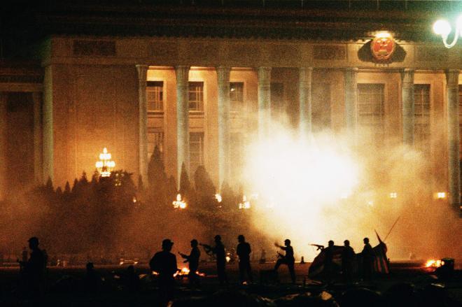 1989年6月4日午前5時ごろ、天安門広場を制圧したあとも、周辺に残る学生・市民に向かって発砲を続ける戒厳軍。後方の建物は人民大会堂