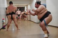 花道の奥で出番を待つ力士たち。十両以下の取組は、幕内力士ほど時間をかけずに進んでいくのでお相撲さんたちが列をなす=恵原弘太郎撮影