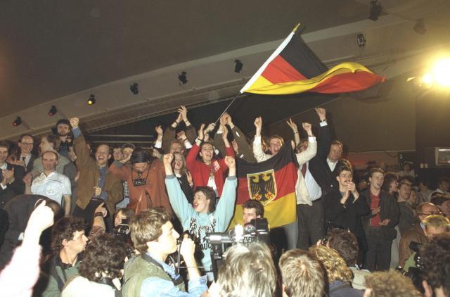 「ベルリンの壁」が崩れて民主化が進む東ドイツで初めての自由選挙が1990年3月18日行われ、西ドイツへの編入による早急な統一を主張してきたキリスト教民主同盟(CDU)など3党で構成する保守派のドイツ連合が過半数に迫る議席を獲得して圧勝した。写真は、パーティーを開き、西独旗を振って大喜びするキリスト教民主同盟の支持者たち