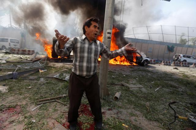 アフガニスタンの首都カブールで起きたテロ事件の現場付近で、両手を広げる男性=2017年5月31日
