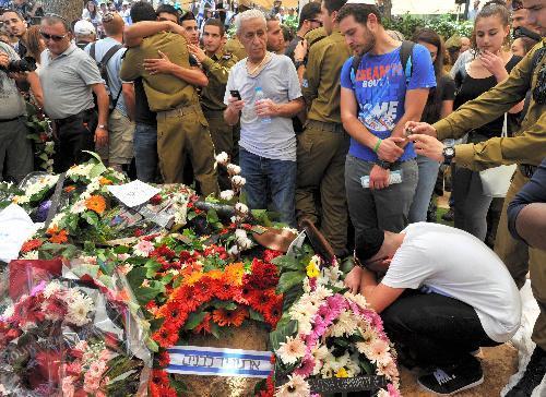「最も悲しい写真」が投稿された同じ頃、戦闘で死亡した兵士の慰霊式で、友人とみられる男性がうずくまっていた=2014年7月23日、エルサレム、仙波理撮影
