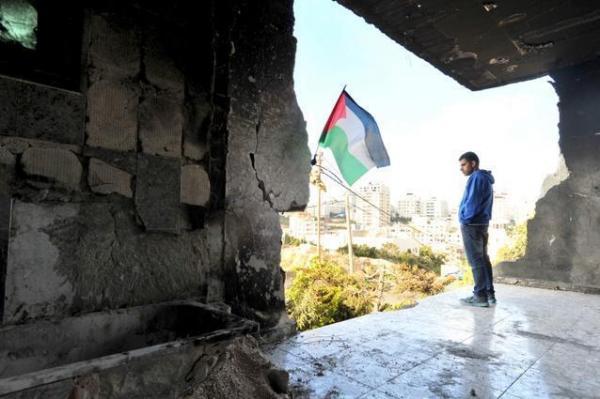 爆発物を使って破壊された、イスラエル人誘拐の容疑者として指名手配されている男性の家。廃屋にはパレスチナ旗が掲げられていた=2014年7月19日、ヨルダン川西岸ヘブロン、仙波理撮影
