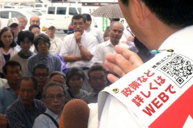 QRコードを入れたタスキをかけて支持を訴える、新顔の候補者=2013年7月4日、宮崎市
